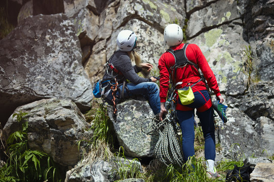 Young women climbers inspect the route before the start of climbing the rock. Female rock climber.
