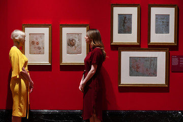 Royal Collection Trust staff pose beside some of Leonardo Da Vinci's anatomical studies at A Life in Drawing in London