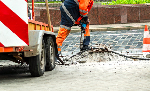 Male worker with full safety equipments drilling and repairing concrete driveway surface with jackhammer.