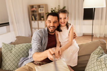 people, family and technology concept - happy father and little daughter taking picture by selfie stick at home