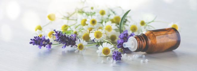 Fläschen Globulis mit Lavendel und Kamille-Banner/Hintergrund für Naturheilkunde und Homöopathie