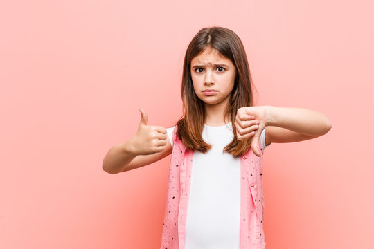 Cute little girl showing thumbs up and thumbs down, difficult choose concept