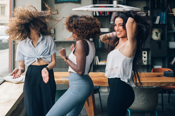 three multiracial women dancing in modern loft