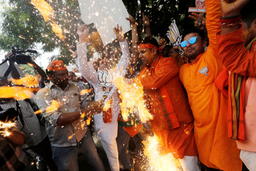 BJP supporters celebrate after learning the initial election results outside the party headquarters in New Delhi