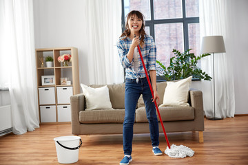 people, housework and housekeeping concept - happy asian woman in headphones with mop and bucket cleaning floor and having fun at home