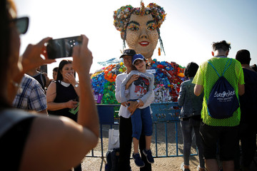People pose for pictures near an artwork as they visit the Eurovision Village, an area dedicated to fans of the 2019 Eurovision Song Contest, in Tel Aviv, Israel