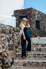 blond woman walking up and down stairs, in a blue jump suit and a sun hat, in Oia on Santorini