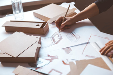 Designer draws a mockup for crafting cardboard box. Development of packaging design sketch.