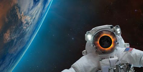 Wall Mural - Solar eclipse on the face of astronaut against spectacular blue earth