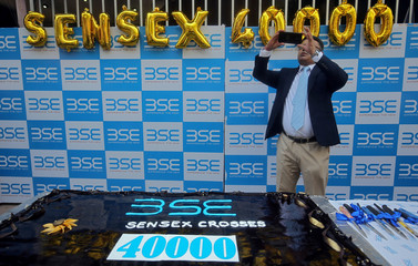 A man uses his mobile phone to take pictures next to a cake to celebrate the Sensex index rising to over 40,000, in Mumbai