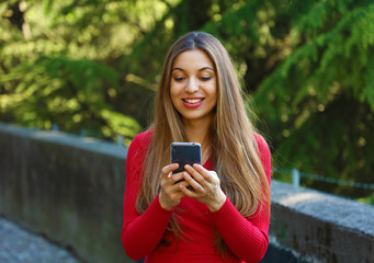 Beautiful young woman using smart phone in the park