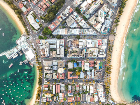 Vertical bird's eye aerial drone panoramic view of the oceanside suburb of Manly, Sydney, New South Wales, Australia. Harbourside on the left, oceanside with famous Manly Beach on the right side.