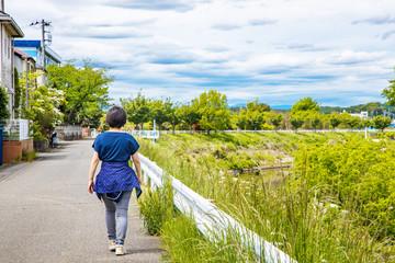 川沿いの遊歩道をウォーキングする女性