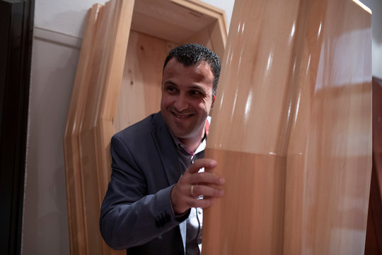 Undertaker and candidate for town councillor at the municipality of Sykies, Konstantinos Baboulas, smiles as he poses inside a coffin at his family's funeral parlor in Thessaloniki