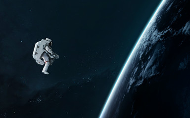 Astronaut orbiting Earth planet, EVA, science fiction image. Elements of this image furnished by NASA