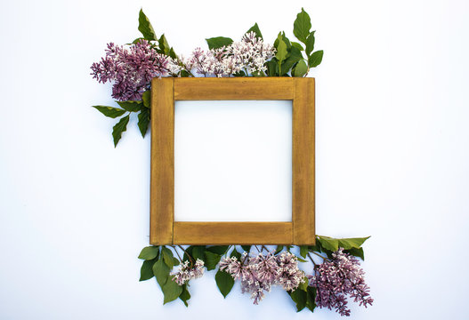 A blank wooden frame mock-up on a white background with lilac flowers and leaves - creative digital flat lay layout