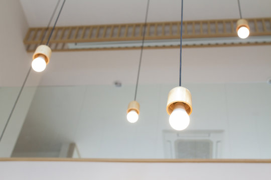 Round warm white LED bulb with wood texture socket lamp hanging from the house ceiling