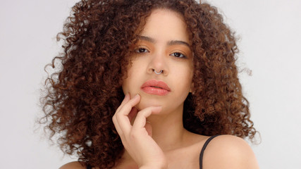 hair blowing closeup portrait of mixed race model with freckles touches her skin