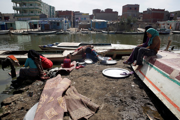 Women of Egypt's Nile Delta village of El Shakhluba wash their household items at the canal, in the province of Kafr el-Sheikh