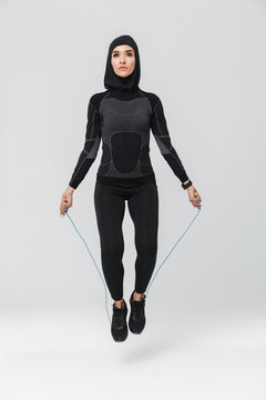 Muslim posing isolated over white wall background make exercises with skipping rope.
