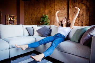 Wall Mural - Full length body size view of her she nice attractive lovely charming cheerful cheery wavy-haired girl sitting on comfortable divan having fun time at industrial loft wooden brick style interior