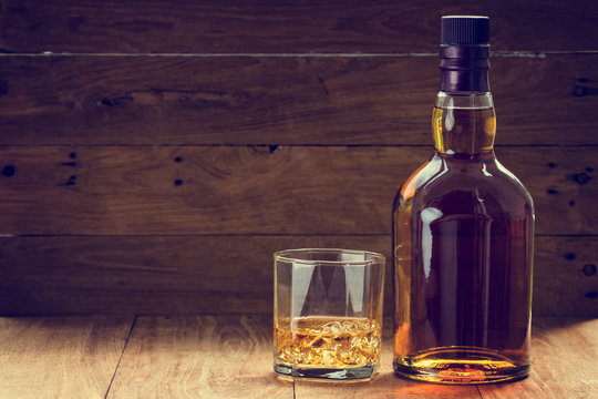 bottle and glass of whiskey  on a wooden background made with vintage tones