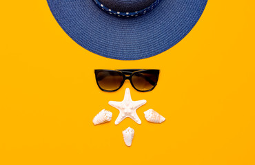 Wall Mural - Summer beach sea accessories. Blue female straw hat, sunglasses, shells, starfish on yellow background top view flat lay copy space. Summer background. Holiday vacation travel concept.