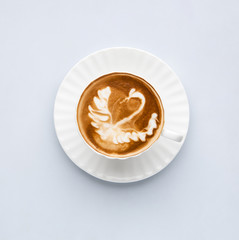 Cup of coffee with the image of a swan on a white background, top view