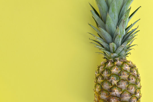 close on a fresh pinapple on yellow background with a copy space on the left