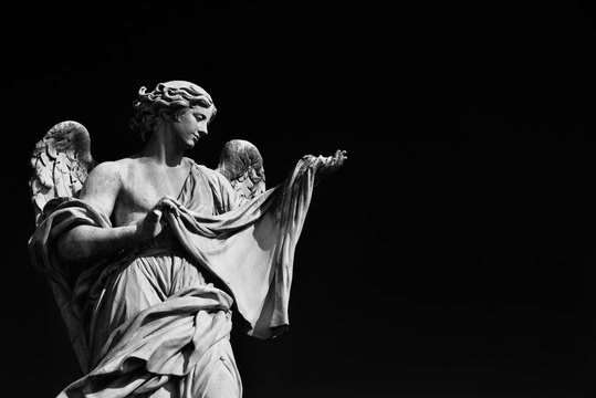 Angel statue holding the Holy Veil.  A 17th century baroque masterpiece at the top of Sant'Angelo Bridge in the center of Rome (Black and White with copy space)