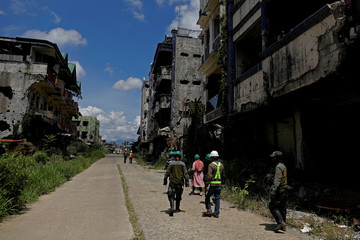 Internally displaced people walk with safety managers during a scheduled visit to the most affected war-torn area of Marawi City