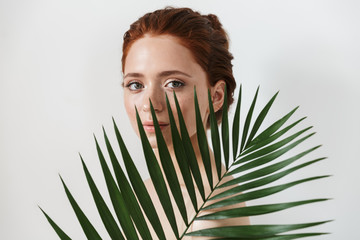 Young redhead woman posing isolated over white wall background with leaf green flowers. Wall mural