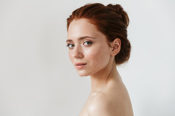 Young redhead woman posing isolated over white wall background.