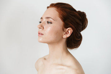Young redhead woman posing isolated over white wall background. Wall mural