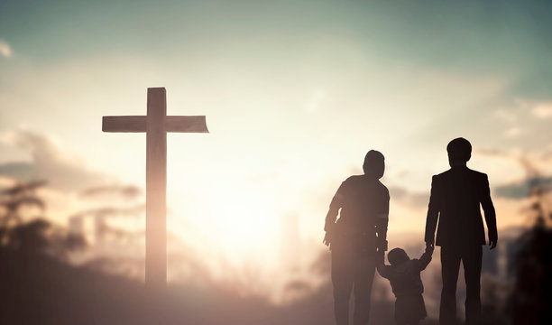 Family worship and praise concept: family praying before the cross