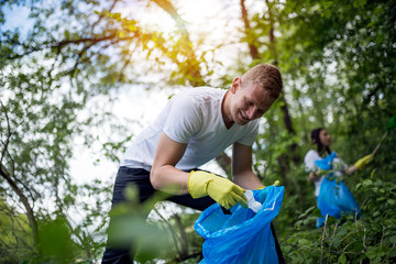 Man volunteer cleaning up the trash in nature.Ecology concept