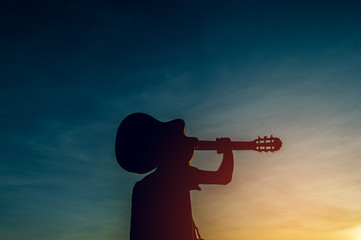 Silhouette of a guitarist in the shadows at sunset light, silhouette concept.