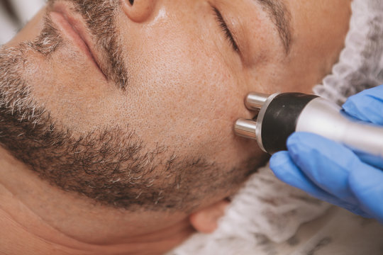 Cropped close up of a mature bearded man relaxing, getting rf-lifting treatment at beauty clinic. Professional cosmetology using rf-lifting machine on a male client. Anti-aging therapy conceptreatment