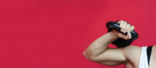 Muscular young woman holding old heavy kettlebell weight with her hand  on her shoulder for hard core workout in the gym against red wall with free copy space