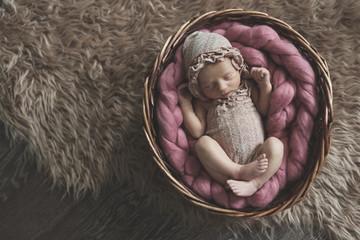 Newborn girl sleeping in basket, dark tone. Posing