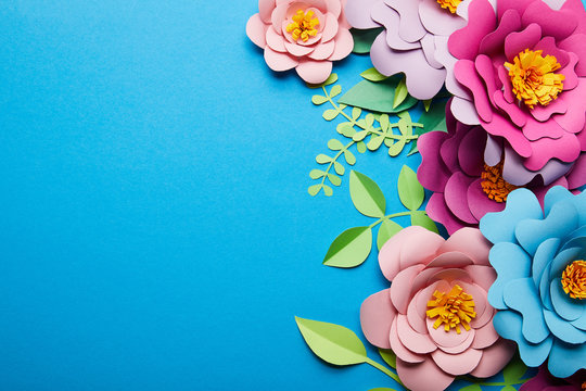 top view of colorful paper cut flowers with green leaves on blue background with copy space