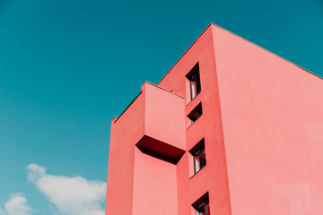 View from below on a pink modern house and sky. Vintage pastel colors, minimalist concept. Wall mural