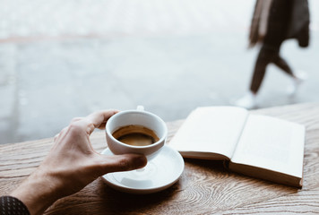 Human hand holding black coffee on saucer with vintage book on background on the wooden table next to big coffee shop window and looking to passerby street walkers