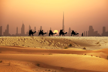 Keuken foto achterwand Dubai Camel tourists caravan walking on sunset desert near Dubai skyline