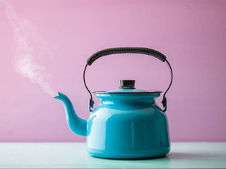 Steaming kettle with boiling water against pink background Wall mural