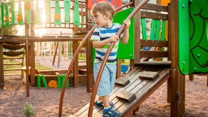 Portrait of active little boy crawling and climbing on wooden staircase on children playground at park