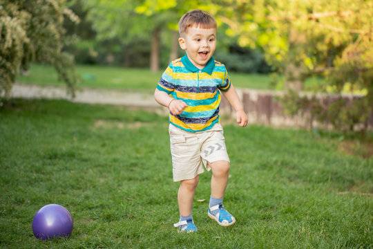 Happy little boy playing with inflatable ball on the grass in the park
