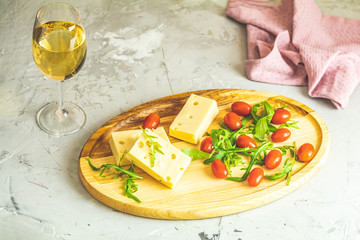 Cheese, tomatoes and arugula on the wooden plate