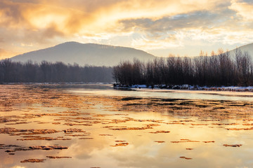 river in mountain at winter sunset. floating melting ice. cloudy sky reflecting in the water surface. wonderful nature scenery