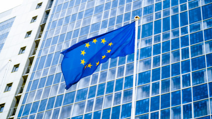 Image of EU flag fluttering on wind against high business office building made of concerete and glass. Concept of ecenomics, development, government and politics